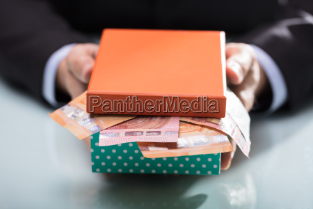 businessperson holding currency notes and boxes