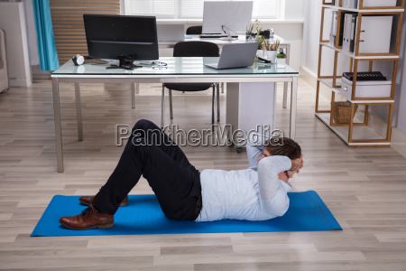 businessman doing exercise on exercise mat