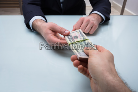 person giving bundle of banknote