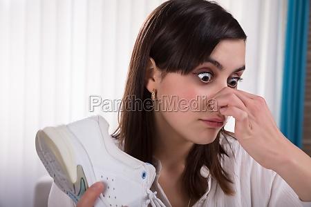 woman holding stinky shoe