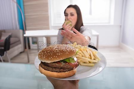 frau die ungesundes lebensmittel beim essen