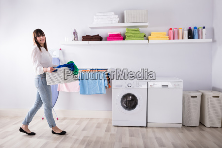 woman carrying basket full of dirty