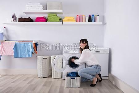 frau die schmutzigen stoff in waschmaschine
