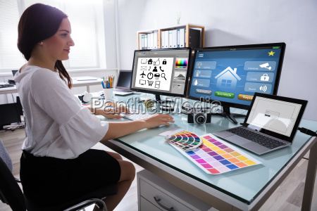 weiblicher designer der an mehrfachem computer
