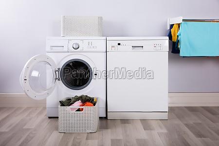 leere waschmaschine mit stapel der schmutzigen