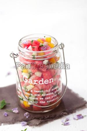 bunter pikanter wassermelonensalat auf weissem holz