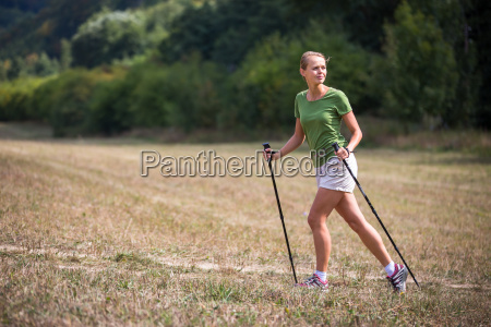 pretty young woman nordic walking on