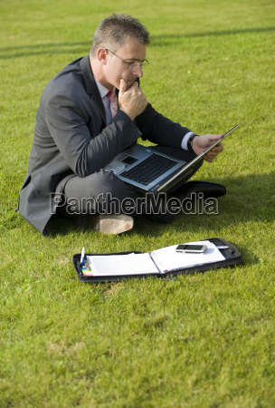 business man sits with laptop in