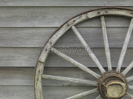 old wooden wheel leans against the