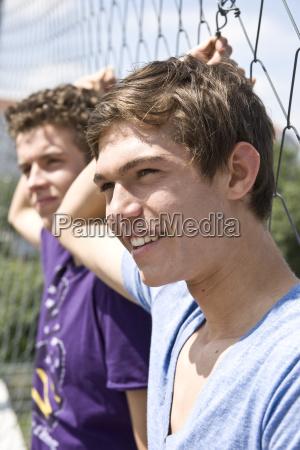 zwei jungs lehnen lassig an einem