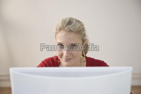 weiblicher teenager arbeitet lachelnd am computer