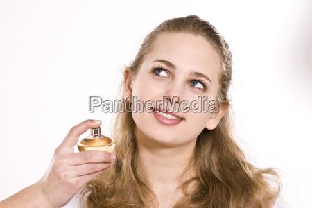 weiblicher teenager bespruht sich mit parfum