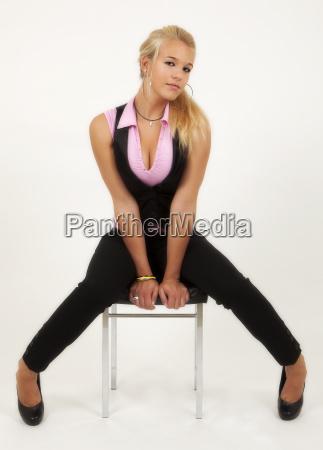 junge frau posiert sitzend auf stuhl
