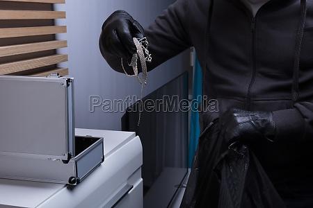 raeuber traegt handschuhe die schmuck stehlen