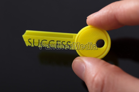 businesspersons hand holding yellow key