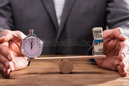 businessperson balancier stoppuhr und aufgerollte banknoten