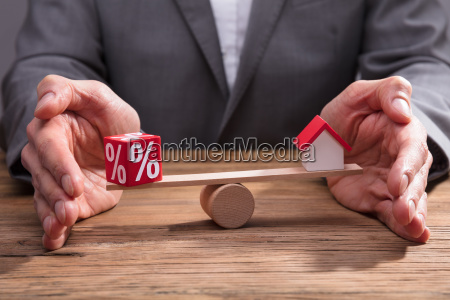 businessperson protecting balance between percentage and