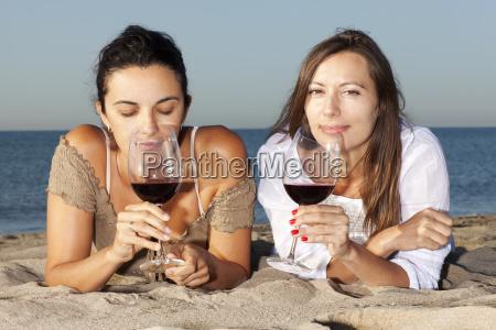 zwei junge frauen trinken wein am
