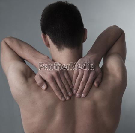 junger mann hat ruckenschmerzen nackenschmerzen
