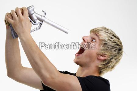 junger mann halt zapfpistole vor offenen