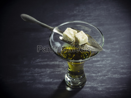 glass of absinthe with traditional spoon