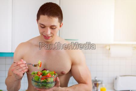 bodybuilder young man eats food salad