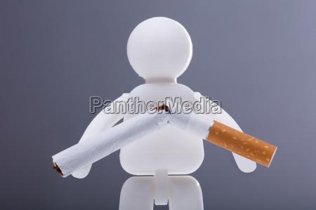 menschliche figur mit zerbrochener zigarette
