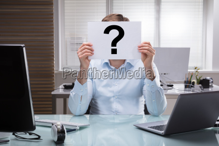 businessperson holding placard with question mark