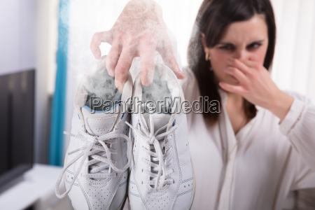 woman holding her smelling exercise shoe