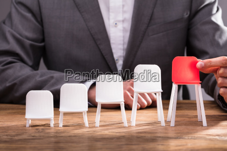 human hand holding red chair