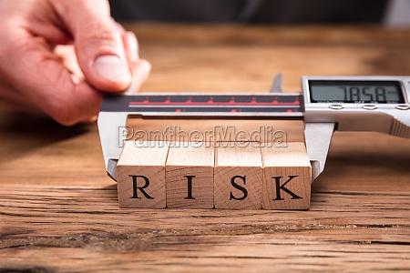 mano humana midiendo riesgos bloques de