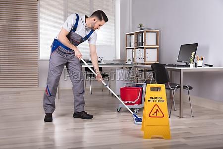 mann reinigung hartholz boden im buero