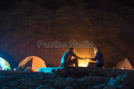 couple sitting by campfire while camping