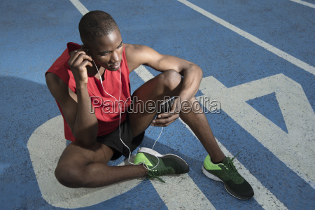 male athlete sitting on all weather