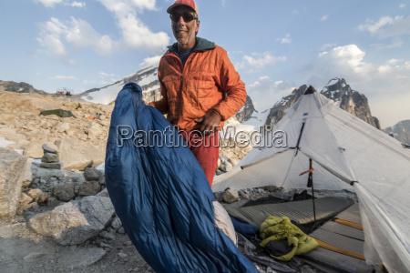 mountain climber standing near tent at