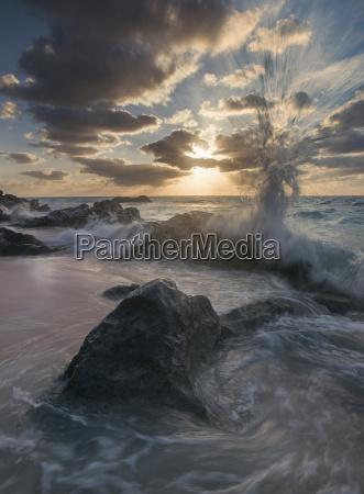 wave crashing on rocks at beach