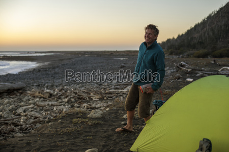 smiling man standing near camping tent