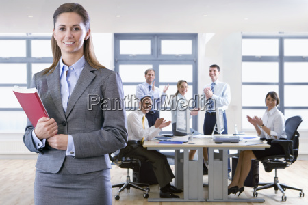 colleagues applauding businesswoman in office meeting