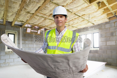 portrait of architect with plans on