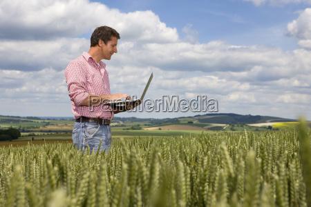 farmer standing in wheat field using