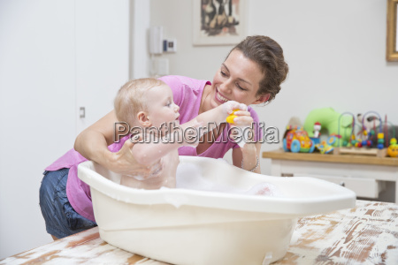 mother washing baby son in plastic