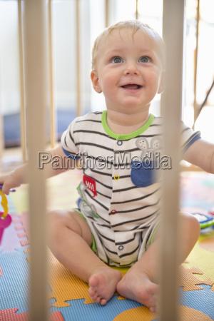 smiling baby boy in wooden playpen