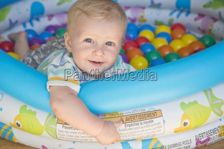 baby boy playing in paddling pool