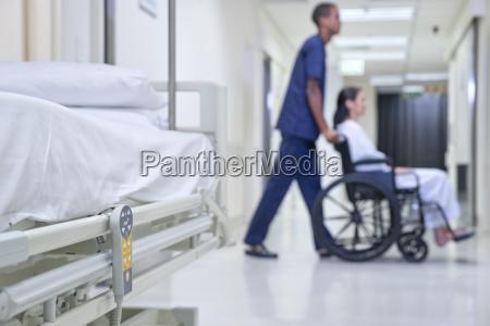 male nurse pushing patient along hospital