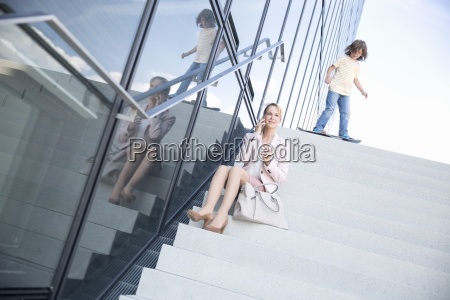 businesswoman mother on phone as son