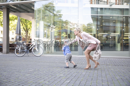 businesswoman pulling reluctant son along outside