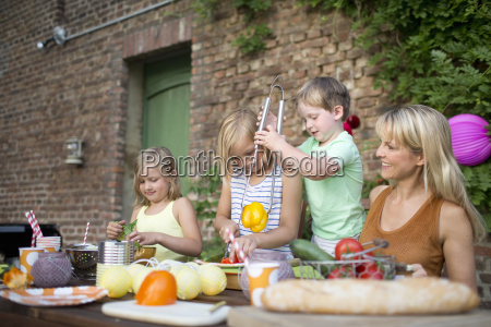 mother with children eating meal outdoors