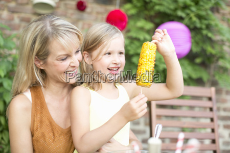 mother with daughter eating sweetcorn at