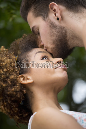 romantic young couple kissing in countryside