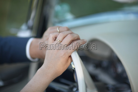 bride and grooms hands on car